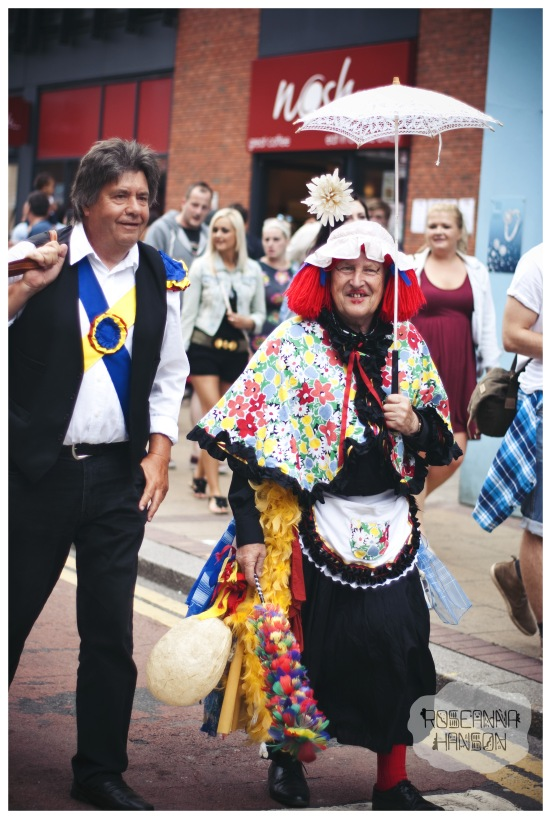 An unusual looking character leading a progression of Morris dancers