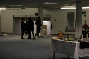 Fiona Halliday's painting hangs in the background, behind exhibition visitors.